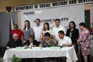 DSWD Secretary Judy M. Taguiwalo (3rd from left), DOH Undersecretary Gerardi Bayugo (right) and NCDA Executive Director Carmen R. Zubiaga (2nd from let) sign the IRR of RA 10754.  Witnessing the signing are principal authors of the law, former Rep. Martin Romualdez (3rd from left) and Sen. Sonny Angara (3rd from right), Cong. Yedda Romualdez (2nd from left), Rep. Imelda Calixto-Robiano (center), DSWD Undersecretary Florita Villar (foremost right), Tahanang Walang Hagdanan President  Mr. Manuel V. Agcaoili (sitted foremost left) and  Liga ng Maykapansanan Mr.  Miguel Catain (standing in red  polo)