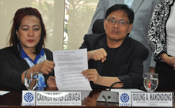 Director Carmen R. Zubiaga of NCDA (right) and Director-General Guiling Mamondiong of TESDA present the signed agreement providing free skills training for persons with disabilities