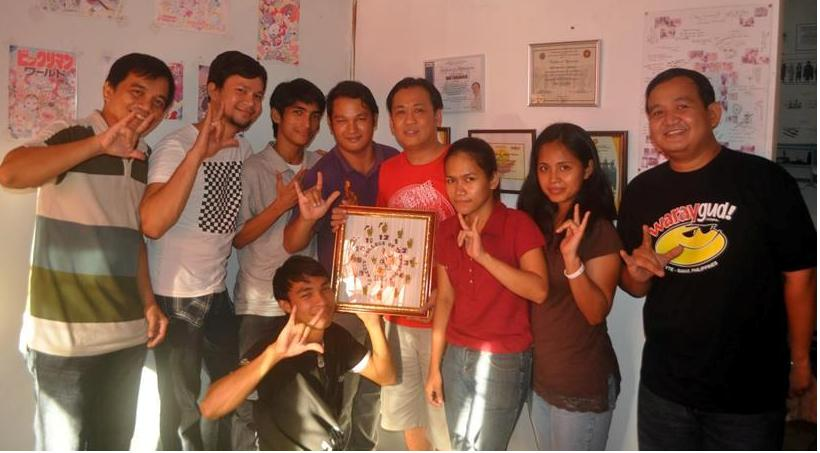 Take One Animation Studio Proprietor/Manager Eric Tansingco (in red shirt, holding the sign language clock) pose together with deaf trainees from MCCID College of Technology