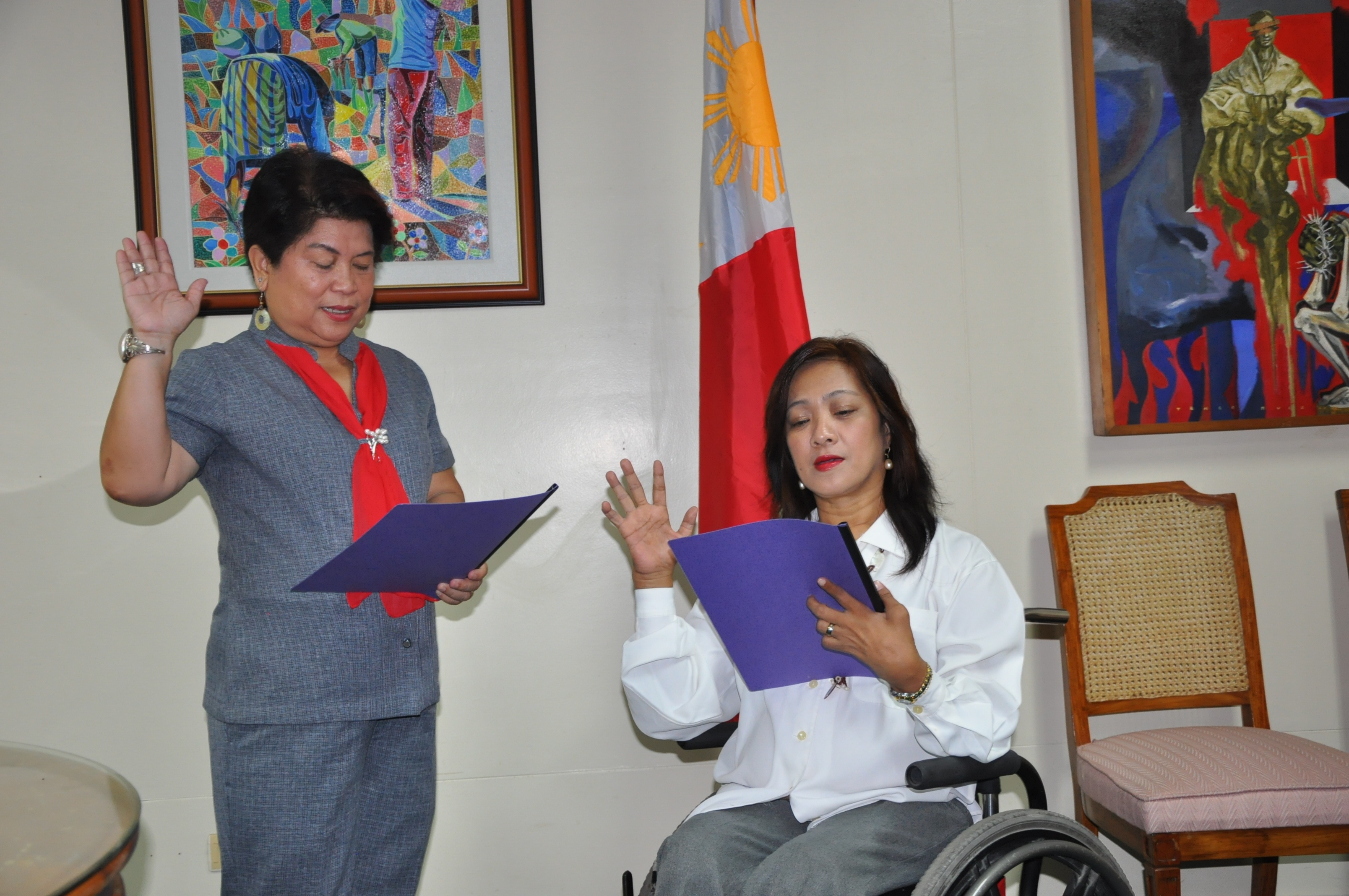 DSWD Secretary Corazon Juliano Soliman administers the oath taking of Ms. Carmen Reyes Zubiaga as the new Acting Executive Director of the National Council on Disability Affairs.