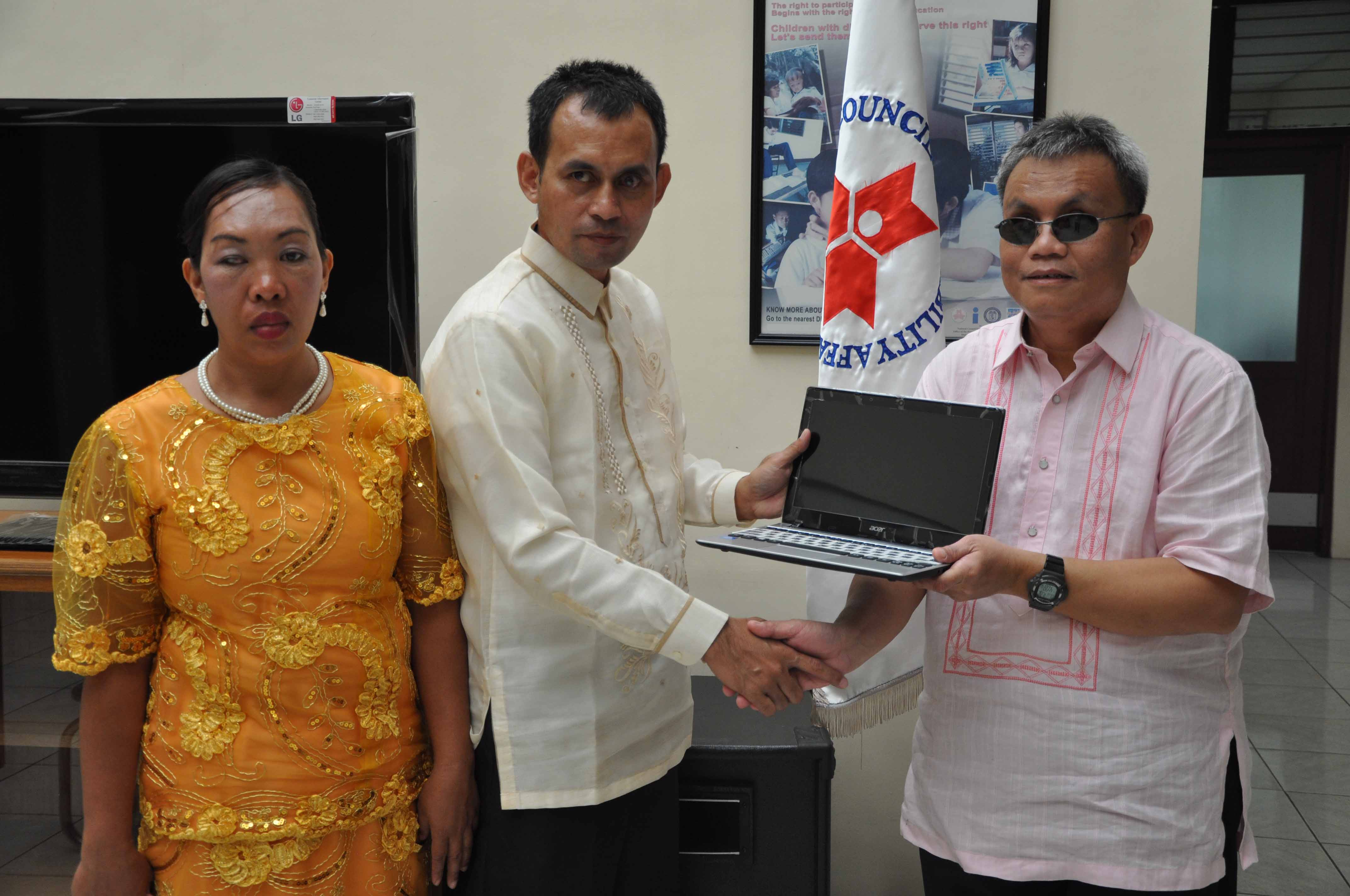 Mr. Teddy Kahil receiving netbooks and tablets